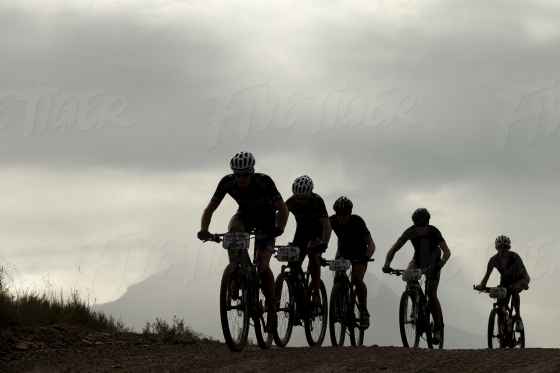 Silhouettes of cyclists coming up a hill
