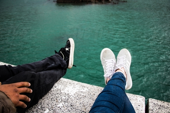 Two pairs of crossed legs with sneakers