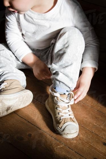 Boy tying his shoe laces
