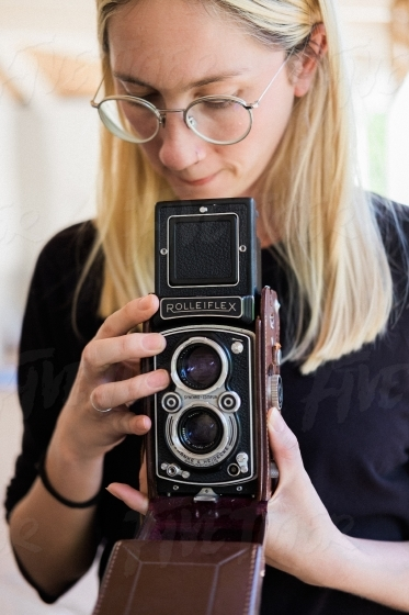 Young blond girl using an old camera