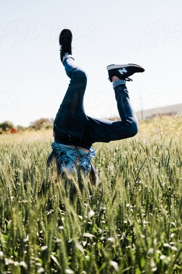 Trendy guy doing a handstand in a wheat field