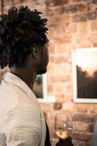 Stylish man dinking wine at an art exhibition