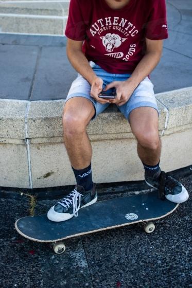 Trendy skateboarder texting