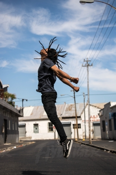 Trendy black man jumping in the street