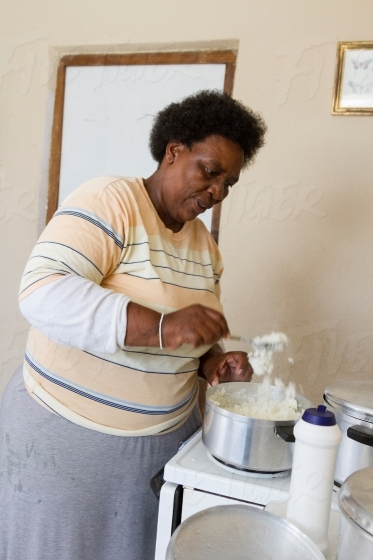 Women at home making mealie meal
