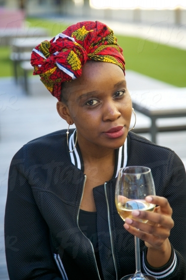 Stylish young woman wearing a head scarf with an African print,