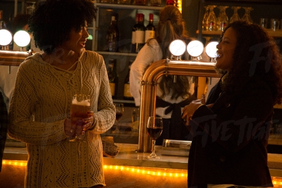 Two women chatting over drinks at a local bar