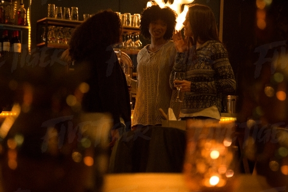 Young women chatting at a bar over drinks