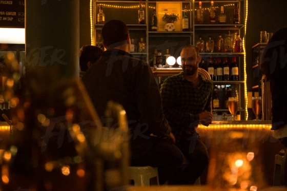 Three men having a drink at a trendy bar