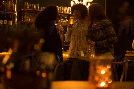 Women chatting at a bar over drinks