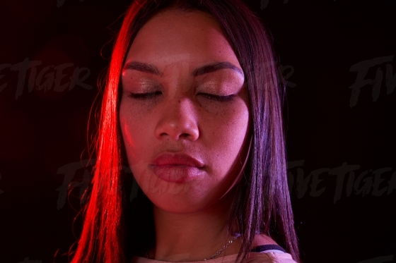 Beautiful young girl lit with red and purple gels in studio
