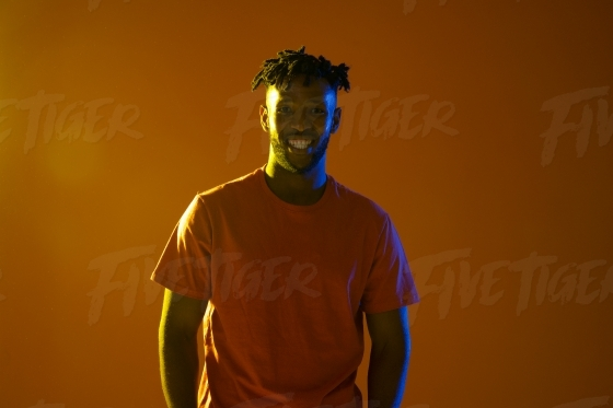 Portrait of an attractive young man lit with yellow and blue gel lighting technique and a lens flare