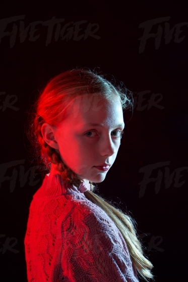 Artistic studio portrait of a blonde tween, lit with blue and red gels