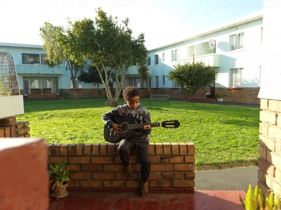 Young boy playing his guitar