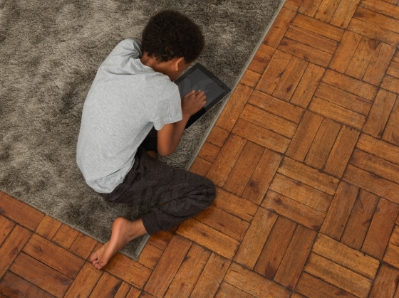 Young boy playing on his tablet on the carpet