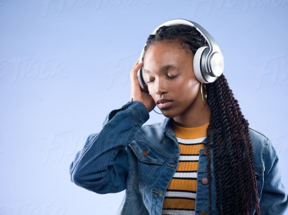 Beautiful young woman listening to music on her earphones