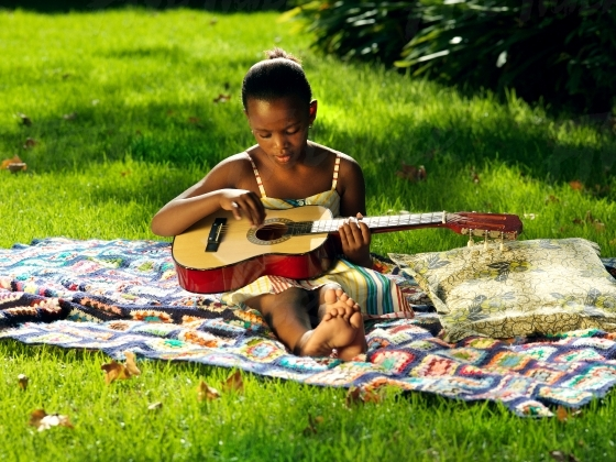 Young girl playing her guitar