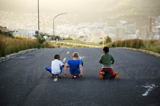 Three kids playing playing outside in the neighbourhood