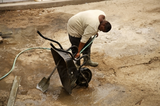 Construction worker cleaning a wheel barrow