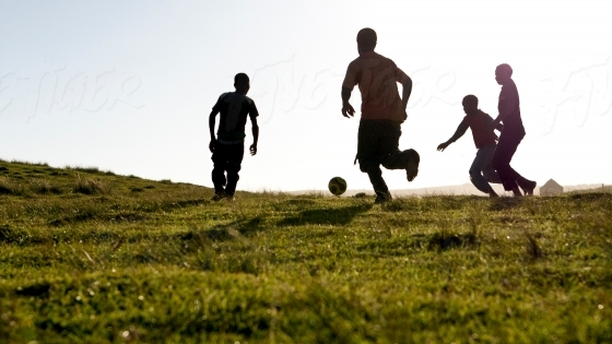 Boys playing soccer on a hilltop