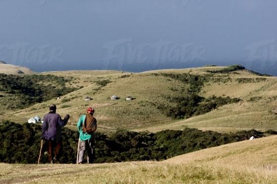 Two elderly men talking as they walk with walking sticks in Eastern Cape