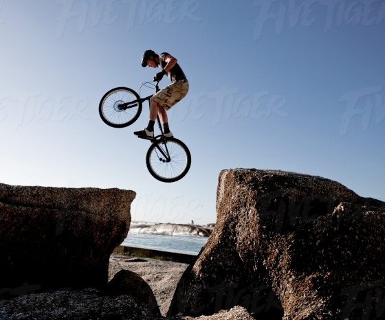 Man jumping across rocks on a trick bicycle