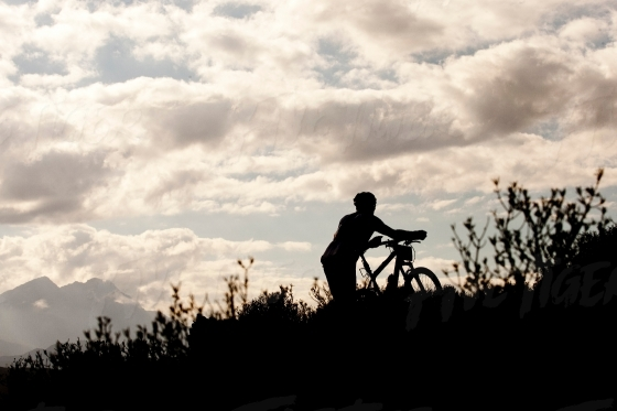 Silhouette of cyclist walking with his bike